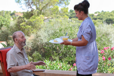 caregiver serving meal to a senior