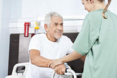 Young female caregiver helping smiling senior